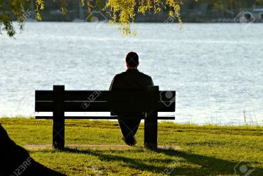 3243528-young-man-sitting-alone-on-park-bench-looking-down-to-the-river-in-late-afternoon-stock-photo